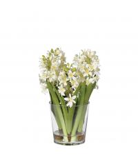 frühlingshafter Blumenstrauß in kleiner Vase aus Glas, weiß