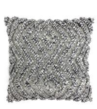 graue Kissenhülle aus grob gewebtem Stoff mit erhabenem Aztekenmuster
