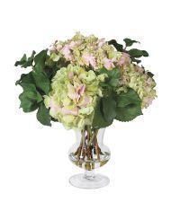 frühlingshaftes Kunstblumengesteck aus Hortensien mit bauchiger Glasvase