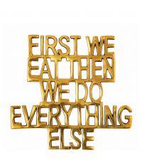 gold glänzender Topfuntersetzer aus poliertem Messing mit Schriftzug 'First we eat ...'