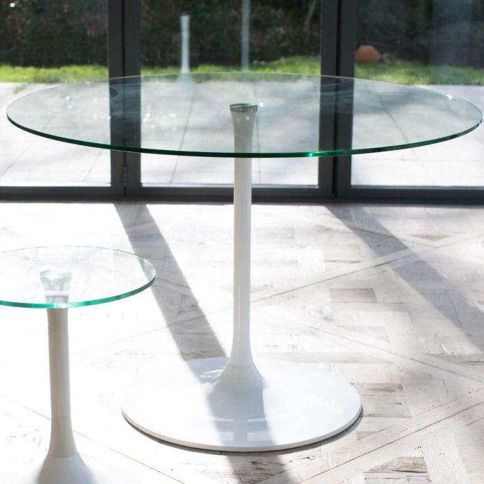 moderner, runder Esstisch aus klarer Glasplatte und Tischfuß in weißem Hochglanz